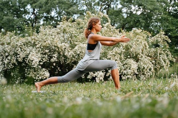 Jovem esbelta praticando ioga no quintal da casa no verão, alongamento e equilíbrio das pernas