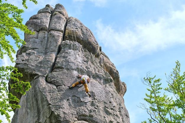Jovem escalando a parede íngreme da montanha rochosa. alpinista masculina supera rota desafiadora. envolvendo-se no conceito de esporte radical.