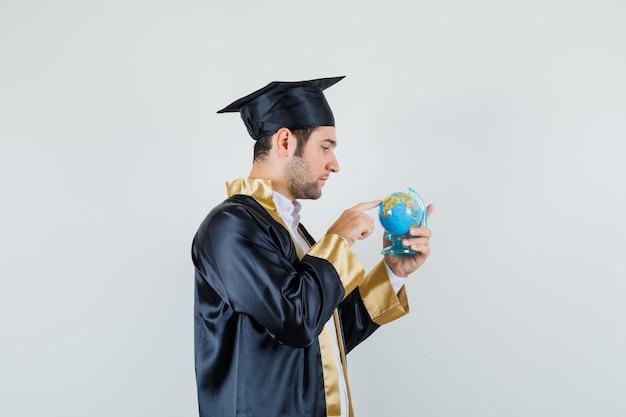Jovem, escolhendo o destino no globo da escola em uniforme de pós-graduação e procurando focado. .