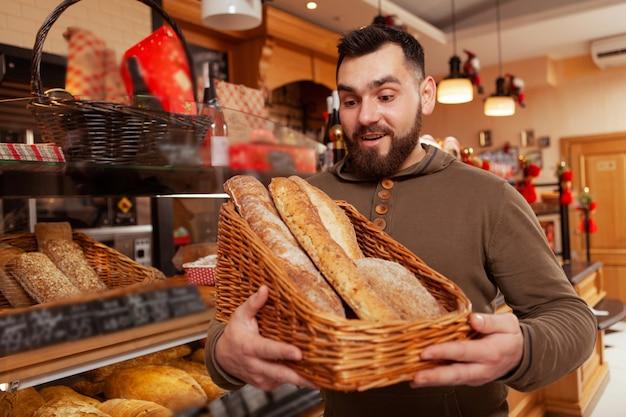 Jovem escolhendo pão fresco da cesta na padaria