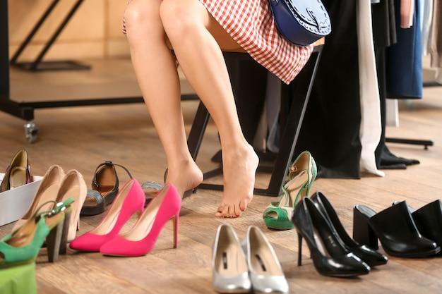 Jovem escolhendo sapatos novos na loja
