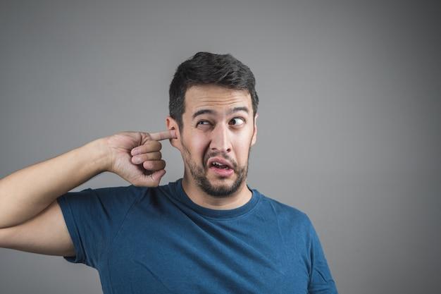 Jovem, escolhendo sua orelha com o dedo