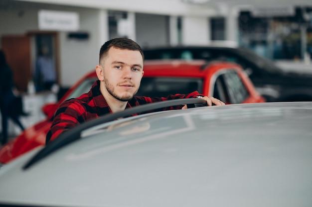 Jovem, escolhendo um carro em uma sala de exposições