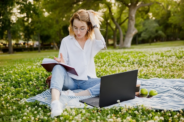 Jovem escrevendo algo no caderno no parque
