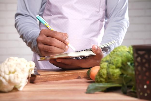 Jovem escrevendo dieta pan no bloco de notas na mesa da cozinha