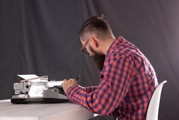 Jovem escritor estiloso trabalhando em uma máquina de escrever