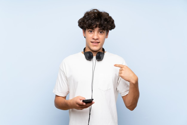 Jovem escutando música com um celular sobre parede azul isolada com expressão facial de surpresa