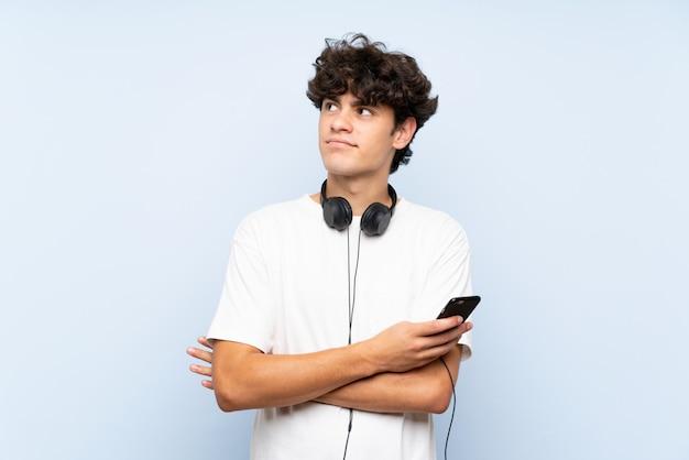 Jovem escutando música com um celular sobre parede azul isolada, olhando para cima enquanto sorrindo