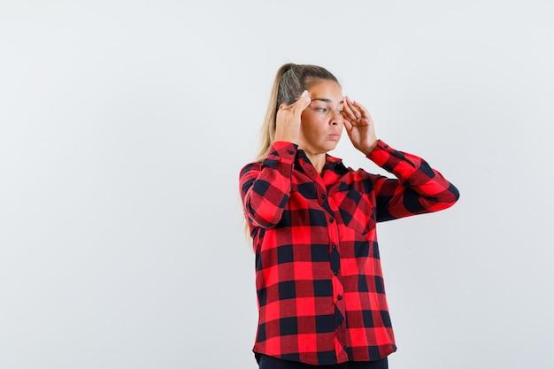 Jovem esfregando as têmporas na camisa casual e parecendo angustiada. vista frontal.