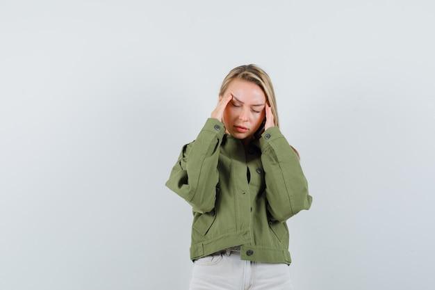 Jovem esfregando as têmporas na jaqueta, calça e parecendo cansada, vista frontal.