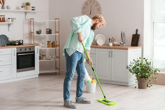 Jovem esfregando o chão na cozinha