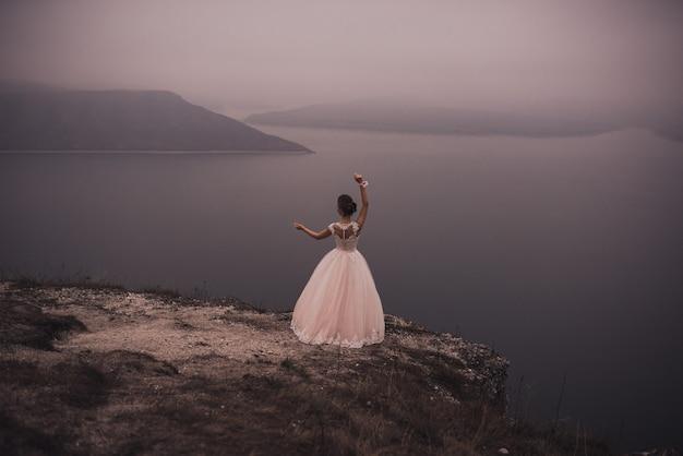 Jovem esguia e linda noiva com um penteado alto e enfeite grego