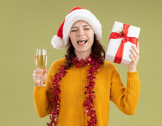 Jovem eslava alegre com chapéu de papai noel e guirlanda em volta do pescoço tira a língua segurando uma taça de champanhe e uma caixa de presente de natal isolada em um fundo verde oliva com espaço de cópia