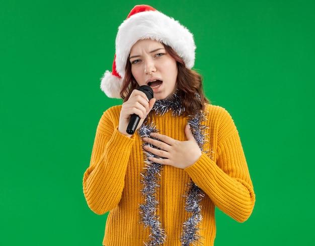Jovem eslava confiante com chapéu de papai noel e guirlanda no pescoço segura o microfone fingindo cantar isolado em um fundo verde com espaço de cópia