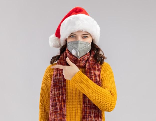 Jovem eslava confiante com chapéu de papai noel e lenço no pescoço e máscara médica apontando para o lado