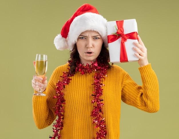 Jovem eslava insatisfeita com chapéu de papai noel e guirlanda em volta do pescoço segurando uma taça de champanhe e uma caixa de presente de natal isolada em um fundo verde oliva com espaço de cópia