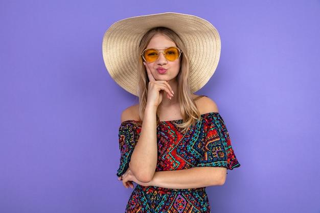 Jovem eslava loira confusa com óculos escuros e chapéu de sol, colocando a mão no queixo e olhando para frente