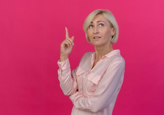 Jovem eslava loira impressionada em vista de perfil, olhando e apontando para cima, isolada em um fundo rosa com espaço de cópia