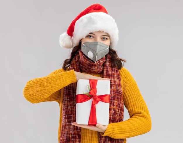 Jovem eslava satisfeita com chapéu de papai noel e lenço no pescoço usando máscara médica segurando uma caixa de presente de natal isolada na parede branca com espaço de cópia