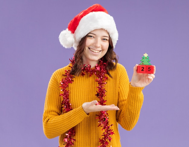Jovem eslava sorridente com chapéu de papai noel e guirlanda em volta do pescoço segurando e apontando para o enfeite de árvore de natal com a mão isolada na parede roxa com espaço de cópia