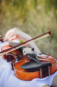Jovem eslava tocando violino na floresta