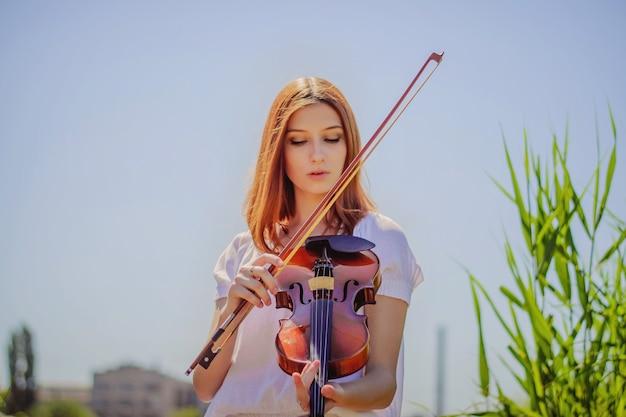 Jovem eslava tocando violino na natureza