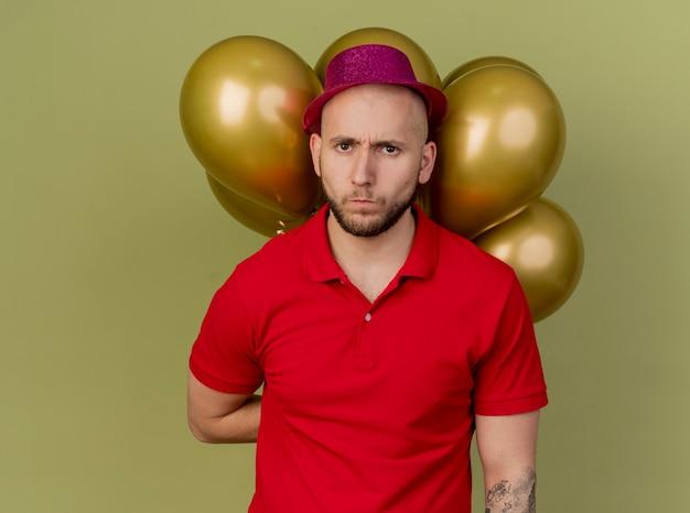 Jovem eslavo bonito carrancudo com chapéu de festa e segurando balões nas costas, isolado em um fundo verde oliva com espaço de cópia