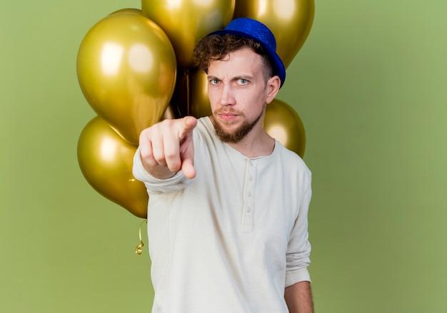 Jovem eslavo bonito carrancudo com chapéu de festa em pé na frente de balões olhando e apontando para a câmera isolada em um fundo verde oliva com espaço de cópia
