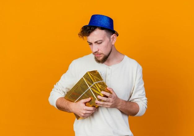 Jovem eslavo bonito carrancudo usando chapéu de festa, olhando para baixo, segurando uma caixa de presente isolada em um fundo laranja com espaço de cópia