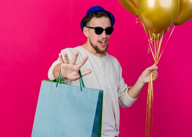 Jovem eslavo bonito desagradável usando chapéu de festa e óculos escuros segurando balões e sacos de papel, olhando para a câmera, sem fazer nenhum gesto isolado no fundo carmesim