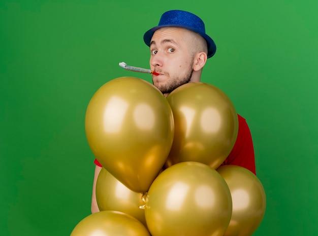 Jovem eslavo bonito festeiro impressionado com chapéu de festa, em pé atrás de balões, olhando para a câmera soprando ventilador de festa