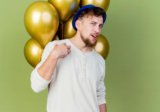 Jovem eslavo bonito festeiro impressionado com chapéu de festa em pé atrás de balões, olhando para a frente, apontando para si mesmo, isolado em uma parede verde oliva com espaço de cópia
