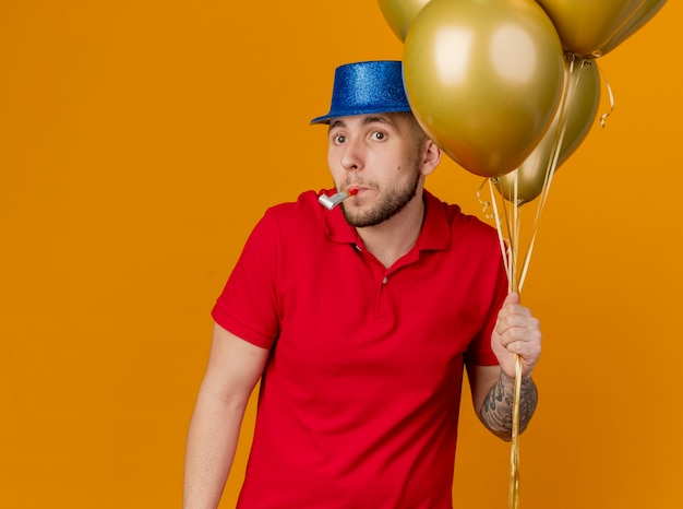 Jovem eslavo bonito impressionado com um chapéu de festa, segurando balões, olhando para o lado, segurando o soprador de festa na boca, isolado em um fundo laranja com espaço de cópia