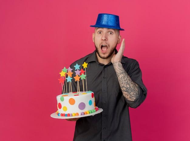 Jovem eslavo bonito surpreso com um chapéu de festa segurando um bolo de aniversário com estrelas segurando as mãos no ar, olhando para a câmera isolada no fundo carmesim com espaço de cópia