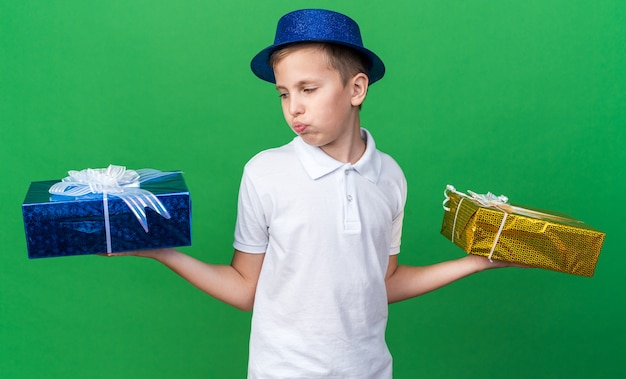 Jovem eslavo confuso com chapéu de festa azul segurando e olhando para caixas de presente isoladas na parede verde com espaço de cópia