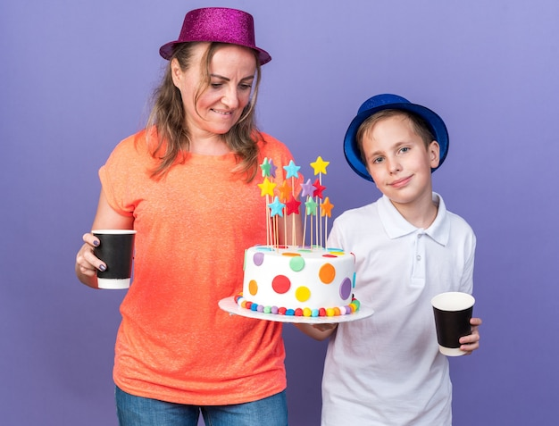 Jovem eslavo satisfeito com um chapéu de festa azul segurando um bolo de aniversário e copos de papel junto com sua mãe usando um chapéu de festa violeta isolado na parede roxa com espaço de cópia