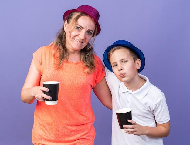 Jovem eslavo satisfeito com um chapéu de festa azul segurando um copo de papel em pé com sua mãe usando um chapéu de festa violeta isolado na parede roxa com espaço de cópia