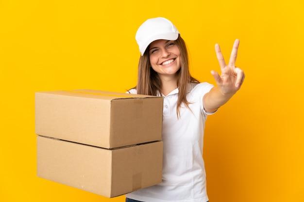 Jovem eslovaca entregadora isolada em um fundo amarelo feliz e contando três com os dedos
