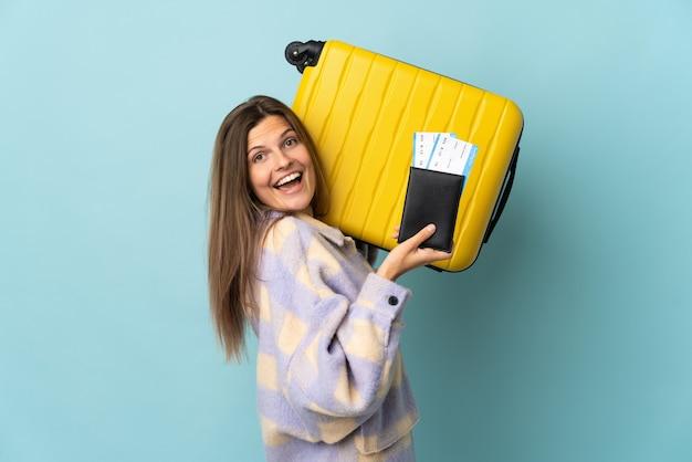 Jovem eslovaca isolada em um fundo azul de férias com mala e passaporte