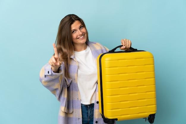Jovem eslovaca isolada em um fundo azul de férias com uma mala de viagem e contando uma
