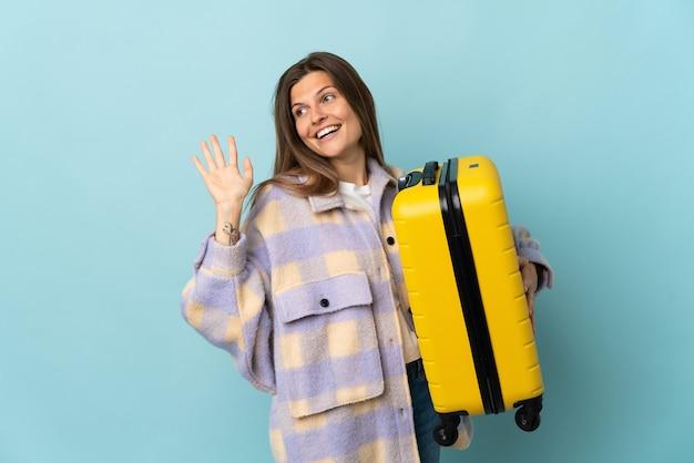 Jovem eslovaca isolada em um fundo azul de férias com uma mala de viagem e saudando