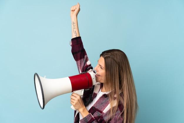 Jovem eslovaca isolada em um fundo azul gritando em um megafone para anunciar algo em posição lateral