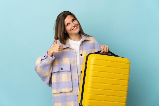 Jovem eslovaca isolada em uma parede azul de férias com uma mala de viagem e com o polegar para cima