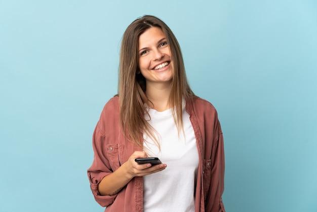 Jovem eslovaca isolada em uma parede azul usando um telefone celular