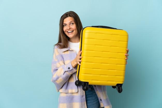 Jovem eslovaca isolada na parede azul de férias com mala de viagem e surpresa