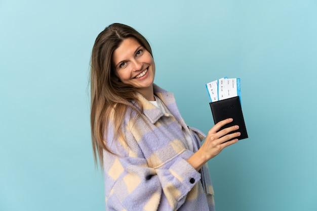 Jovem eslovaca isolada na parede azul feliz nas férias com passaporte e passagens aéreas