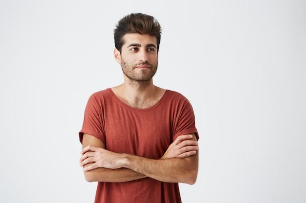 Jovem espanhol hipster vestindo camiseta vermelha ligeiramente sorrindo, mantendo as mãos cruzadas e meditativo olhando de lado durante a sessão de fotos da revista. conceito de beleza, pessoas, juventude e estilo de vida