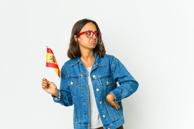Jovem espanhola segurando uma bandeira confusa, sente-se em dúvida e insegura.