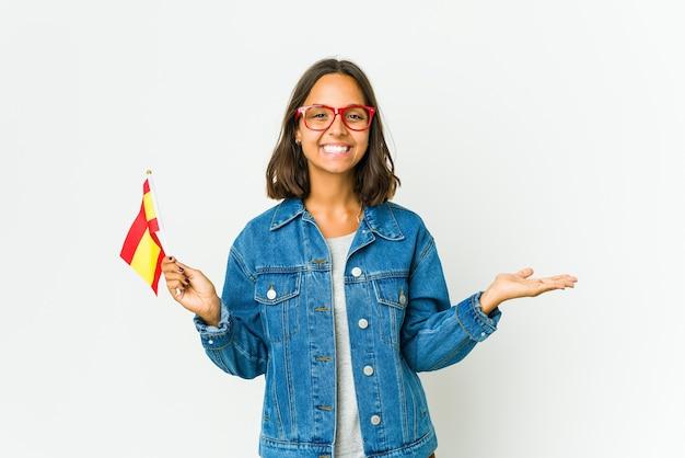 Jovem espanhola segurando uma bandeira isolada na parede branca, mostrando um espaço de cópia na palma da mão e segurando a outra mão na cintura.