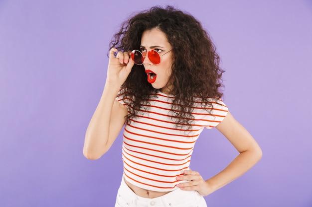 Jovem espantada com cabelos cacheados no desgaste do verão e óculos de sol, olhando de lado
